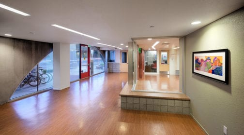 Interior of entrance hall at 801 Alma property featuring glass wall, office, and arch shaped window; bike rack and street visible though window