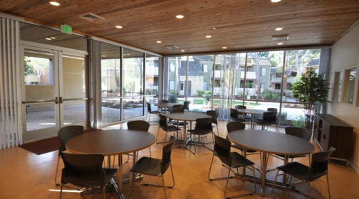 Ashland Village interior of community area including tables, chairs, and large windows