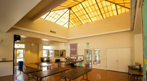 Corona Ranch interior of common area featuring table and yellow tinted industrial glass ceiling