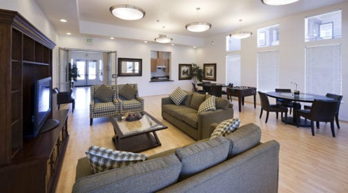Walker Landing interior common area featuring chairs, tables, sofas, and TV